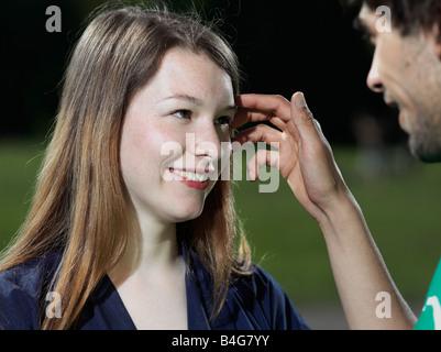 Ein junger Mann die Haare aus dem Gesicht einer jungen Frau zurückschieben - Stockfoto