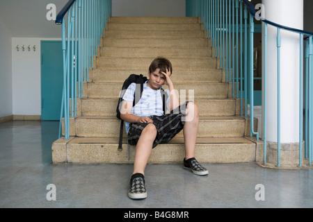 Besorgt 10-13 junge sitzt auf der Treppe in einer Schule