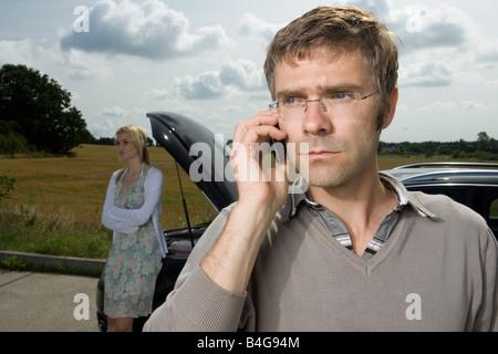 Ein paar steht am Straßenrand neben ihrem Auto kaputt - Stockfoto