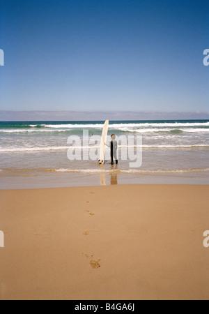 Ein Surfer stehen am Strand mit seinem Surfbrett im Ozean beobachten - Stockfoto