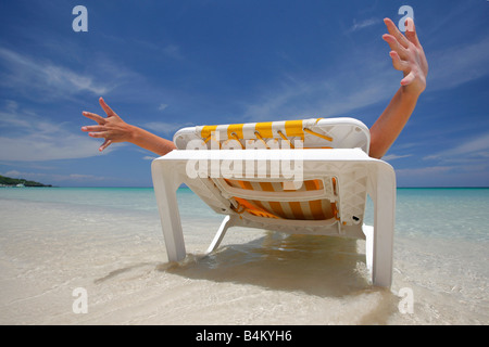 Frau erstreckt sich auf einem Liegestuhl an einem tropischen Strand - Stockfoto