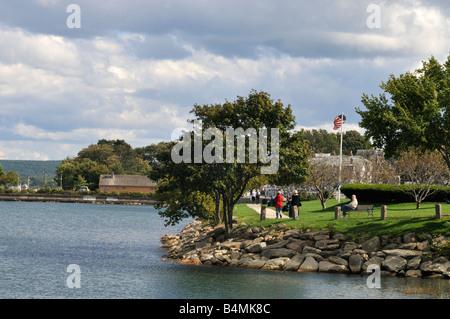 Waterfront Park am historischen Hafen von Plymouth, MA, USA mit Menschen gehen und sitzen auf der Parkbank - Stockfoto