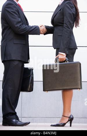 Zwei Geschäftsleute stehen im Freien halten Aktentaschen und Händeschütteln - Stockfoto