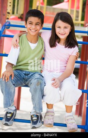 Zwei kleine Kinder sitzen auf Spielplatz Struktur lächelnd (Tiefenschärfe) - Stockfoto