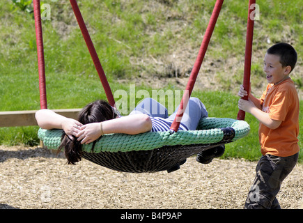 Lächelnd Sohn und Mutter spielen auf einer Schaukel auf dem Spielplatz am Rainham Marshes - Stockfoto