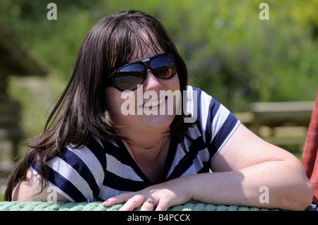 Mutter auf einer Schaukel mit ihrem Sohn Lächeln spiegelt sich in ihrer Sonnenbrille - Stockfoto