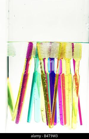 Nahaufnahme von untergetaucht und schwimmenden bunten Zahnbürsten in Glasvase - Stockfoto