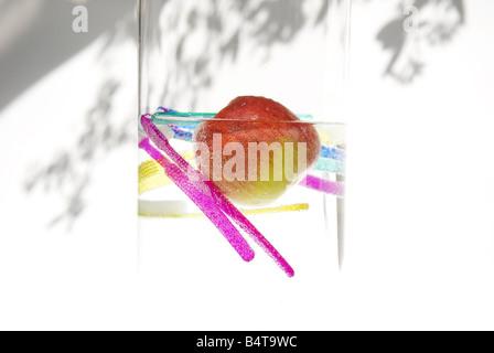 unter Wasser Apfel und schwimmende hell farbige Zahnbürsten in Glasvase mit Pflanze Schatten auf weißem Hintergrund - Stockfoto