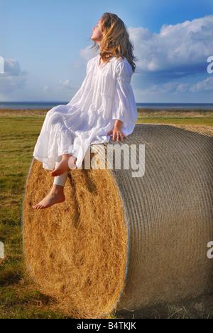 junges Mädchen sitzt auf einem Stroh Rollen - Stockfoto