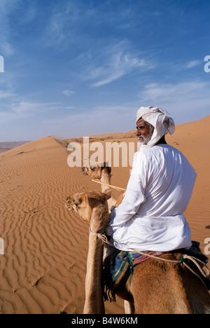 Oman, Wahiba Sands. Eine Beduinen reitet auf seinem Kamel in der Wüste - Stockfoto