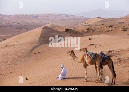 Oman, Sharqiyah, Wahiba Sands. Eine Beduinen kniet in der Wüste beten hält seinen Kamelen durch ihre Halfter zu - Stockfoto