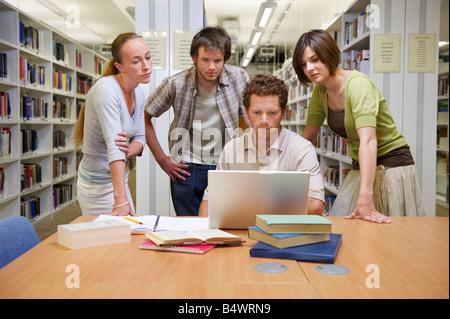 Junge Studenten in einer Bibliothek - Stockfoto