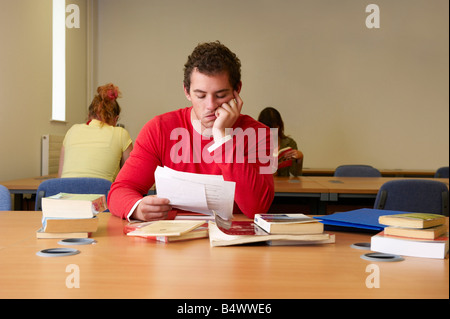 Gelangweilter junger Mann sitzt am Schreibtisch zu studieren - Stockfoto
