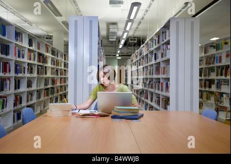 Junge Multitasking Student in Bibliothek - Stockfoto