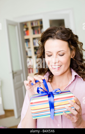 Frau ein Geburtstagsgeschenk zu öffnen - Stockfoto