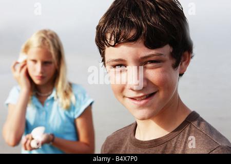 Freunde auf der Suche nach Muscheln am Strand - Stockfoto