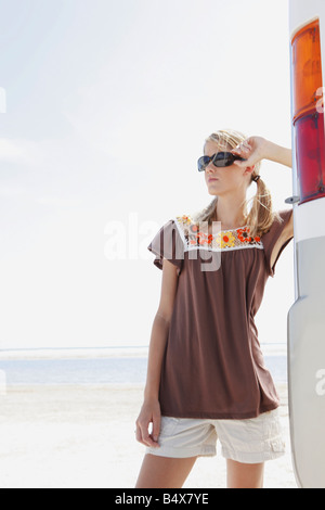 Junge Frau posiert neben Wohnmobil am Strand - Stockfoto