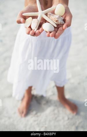 Mädchen am Strand mit zarten Seesterne und Muscheln - Stockfoto