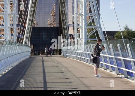 Eine junge männliche College Studentin steht auf der Millennium Bridge über den Manchester Ship Canal und bereitet - Stockfoto