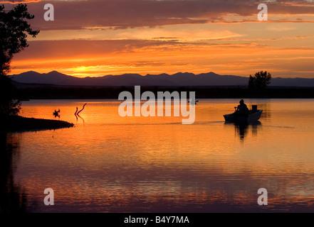 Fischer versuchen ihr Glück von Booten auf dem golden schimmernden See bei Sonnenuntergang nach einem schönen Colorado - Stockfoto