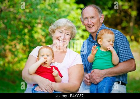 Rothaarige Twin Enkel mit Fokus halten auf glückliche Großeltern - Stockfoto