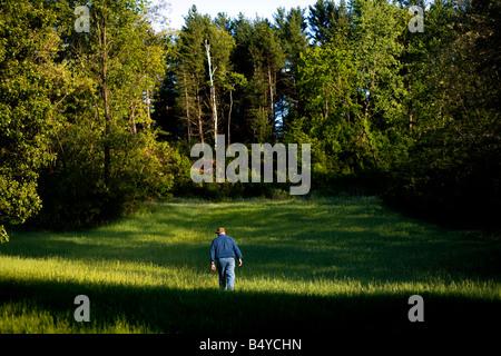 Ein älterer Mann, ein Spaziergang durch Feld im späten Nachmittag Licht - Stockfoto