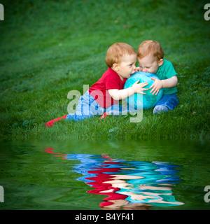 Junge rothaarige Baby jungen draußen auf dem Rasen spielen mit ball - Stockfoto