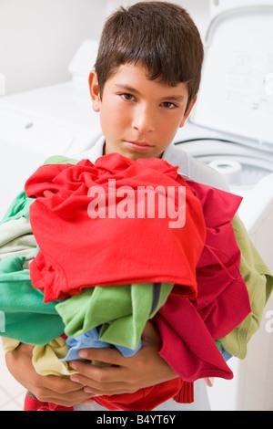 Kleiner Junge hält einen Haufen Wäsche - Stockfoto