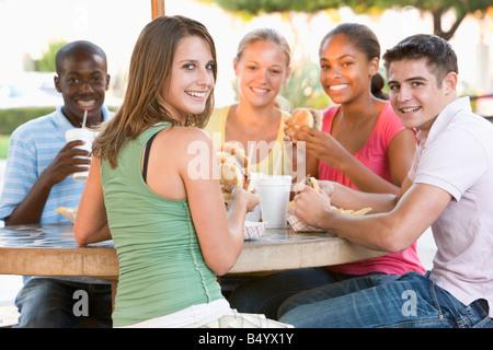 Gruppe von Jugendlichen sitzen im Freien essen Fast Food - Stockfoto