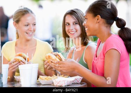 Teenager-Mädchen sitzen im Freien essen Fast Food - Stockfoto
