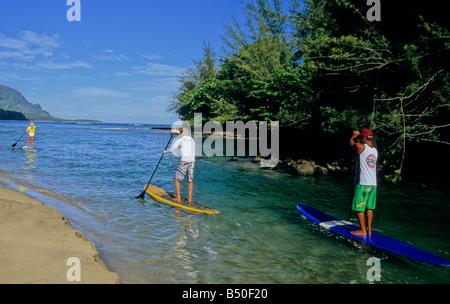 Paddel-Boarder gehen von der Mündung des Hanalei River in Hanalei Bay auf Kauai - Stockfoto