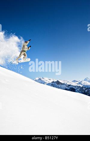 Niedrigen Winkel Blick auf einen jungen Mann Snowboardingan Alpen der Schweiz - Stockfoto
