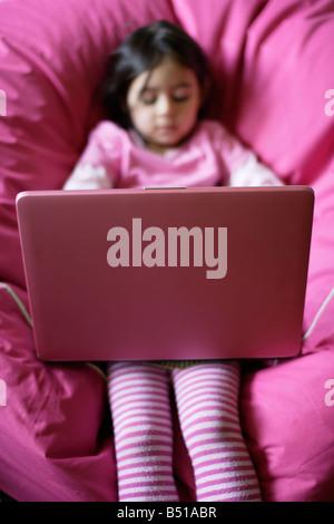 Fünf Jahre altes Mädchen mit rosa Laptopcomputer sitzen auf rosa Sitzsack