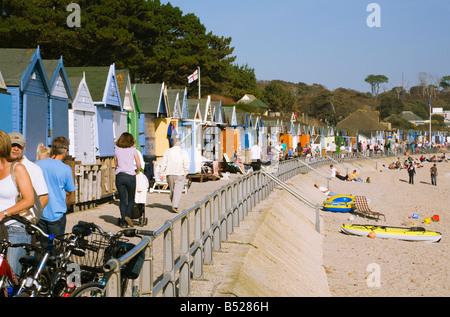 Ansicht von Menschen zu Fuß am Meer. Strand Hütten. Avon Strand, Christchurch, Dorset. VEREINIGTES KÖNIGREICH. - Stockfoto