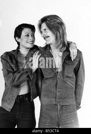 Mode - 1970er Jahren: Das She-Männchen. Sie übernimmt von ihm?; Paar Denim-Jacken und Jeans tragen.; Mann mit langen - Stockfoto