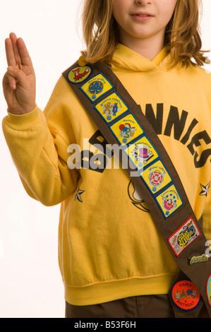 10 Jahre altes Mädchen gekleidet in Brownies einheitliche zeigt ihre Sammlung von Verdienstabzeichen für die Erledigung - Stockfoto