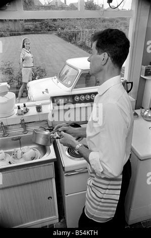 Ein Mann eine Frau in einer Sububan Gegend von Manchester zu Hause lebt. Mann Abwasch Aufgaben zu tun, wie die Frau - Stockfoto