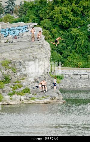 Eine Gruppe von Freunden zu sehen als ein springt von einer hohen Klippe-Damm in einen Fluss. - Stockfoto