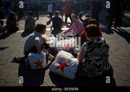 Shopper mit ihren Käufen von Macys machen Sie eine Pause im Union Square Park in New York - Stockfoto