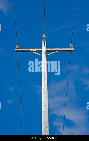 Telefonmast & Stromleitungen gegen blauen Himmel als Symbol für die ...
