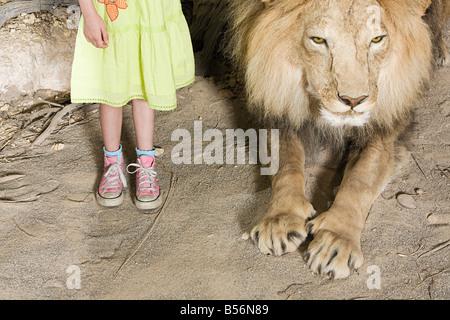 Mädchen stehen neben einem ausgestopften Löwen - Stockfoto