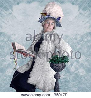 Lady in Feder Hut und Mantel liest ein Kaktus Pflanze - Stockfoto