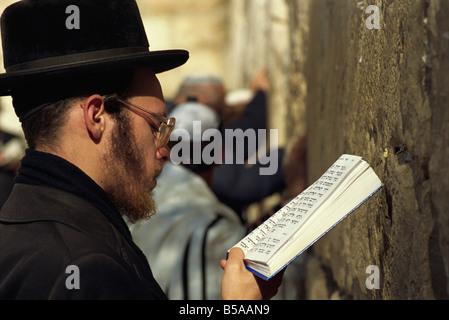 Nahaufnahme von orthodoxen Juden zu beten, mit einem Buch in der Hand an der Klagemauer in Jerusalem, Israel, Nahost - Stockfoto