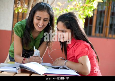 Zwei attraktive Teenagerin Studenten teilen ihren MP3-Player außerhalb im sonnigen Spielplatz Schulcampus - Stockfoto
