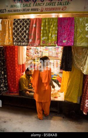 Eine Frau kauft Saris in einem Geschäft in der Kinari-Markt, Alt-Delhi Indien - Stockfoto