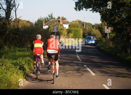 Aktive Erwachsene. Älteres paar Radfahren entlang einer Landstraße an der Grenze von Hampshire und Dorset. VEREINIGTES - Stockfoto