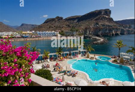Der Pool im Club de Mar in Puerto Mogan mit Sandstrand, Cafés Villen hinter Mogan. Gran Kanaren Canaria Spanien - Stockfoto