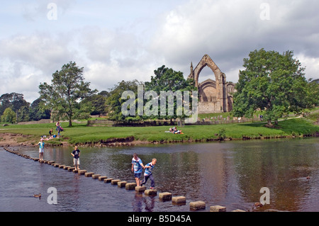 Kinder überqueren die stepping stones jenseits des Flusses Wharfe an Bolton Abbey, Wharfedale, Yorkshire, England - Stockfoto
