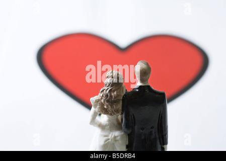 Miniatur Braut und Bräutigam stehen vor großen Herzen Grafik - Stockfoto