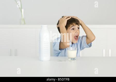 Junge mit verschüttete Milch schreien, die Hände auf den Kopf - Stockfoto
